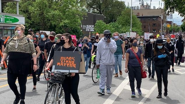 Des manifestants masqués marchent dans une rue de Toronto.