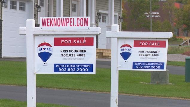 Deux panneaux devant devant des maisons neuves indiquent qu'elles sont à vendre.