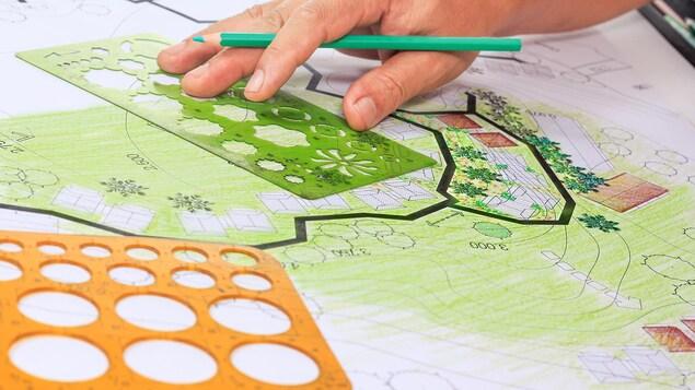 Une main tenant un crayon en train de travailler sur un plan d'un parc avec plusieurs outils de dessins.