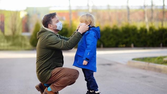 Un père ajuste un masque sur le visage de son fils.
