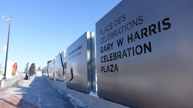 Des panneaux de métal aux inscriptions bilingues bordent une rampe vers la place Gary W Harris.