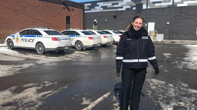 Caroline Garant devant des autos de police.