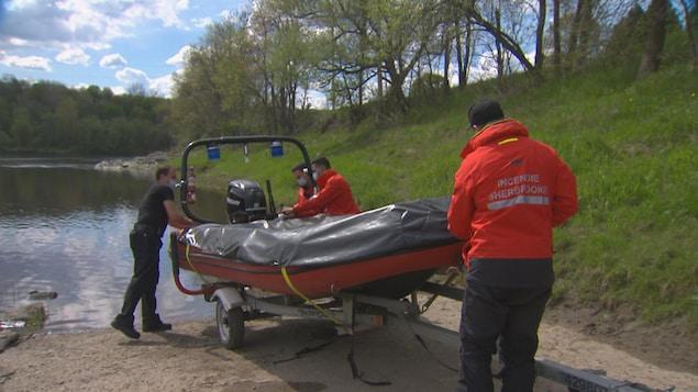 Des pompiers de la Ville de Sherbrooke préparent leur bateau de sauvetage.
