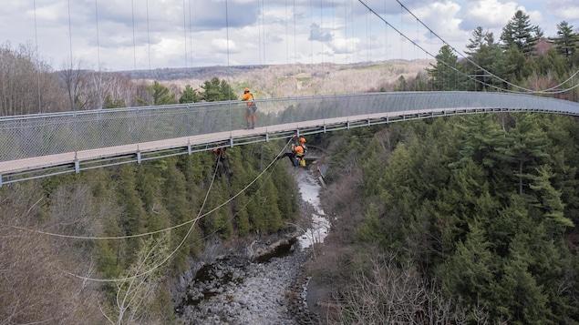 Un ingénieur est accroché sous le pont suspendu, à plusieurs dizaines de mètres de hauteur.