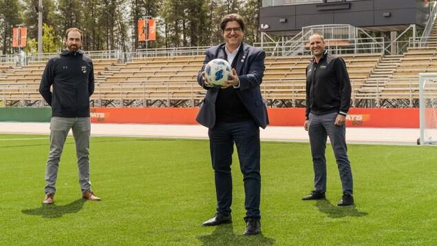 L'entraîneur de la formation masculine de soccer des Patriotes, Shany Black, le recteur de l'UQTR, Christian Blanchette, et le directeur adjoint du Service de l'activité physique et sportive de l'UQTR, Simon Bélanger sur le nouveau terrain de soccer synthétique de l'université.