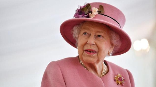 La reine regarde à sa droite. Elle porte un chapeau assorti à sa veste, où figure une broche de fausses fleurs.