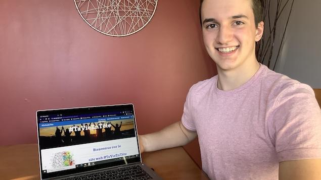 Renaud St-Onge souriant aux côtés d'un ordinateur portable.