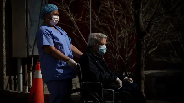 Une employée d'une résidence de soins de longue durée pousse un patient assis sur une chaise roulante. Les deux personnes sont masquées.