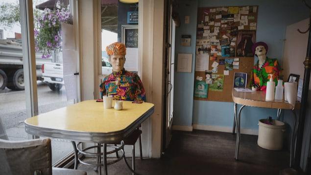 Des mannequins assis à des tables de café.