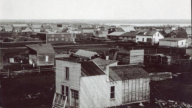 Village sur terre battue avec des bâtisses en construction. Reproduction d'une carte postale.
