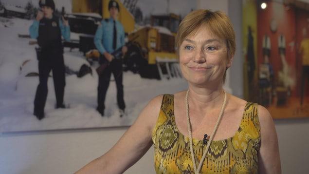 Ségolène Roederer est debout devant des affiches de cinéma.
