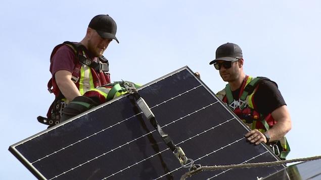 Deux employés tiennent un panneau solaire sur un toit.