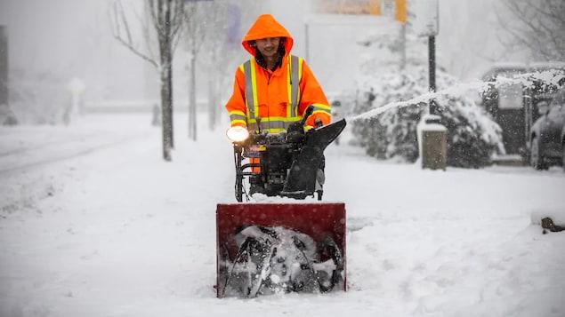 Un homme et sa souffleuse à neige sur le trottoir.   Un homme pousse une souffleuse de neige sur un trottoir du Grand Vancouver très enneigé.