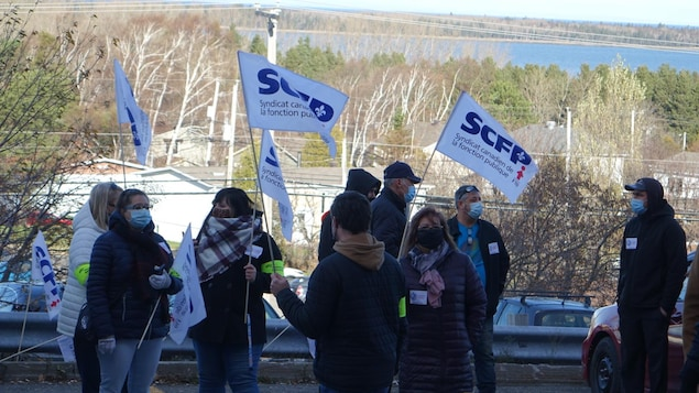 Une dizaines de syndiqués avec des drapeaux aux couleurs de leur syndicat manifestent.