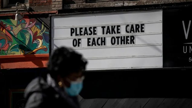 Une femme marche devant une pancarte indiquant de prendre soin les uns les autres.