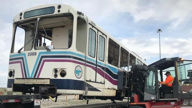 Un wagon de train qui se trouve sur la plate-forme d'un camion est soulevé par un chariot élévateur. Un homme qui porte une veste de sécurité est agenouillé devant le camion et regarde l'opération du cariste.