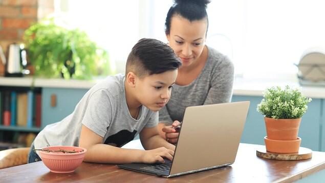 Une femme et un jeune garçon devant un ordinateur portable.
