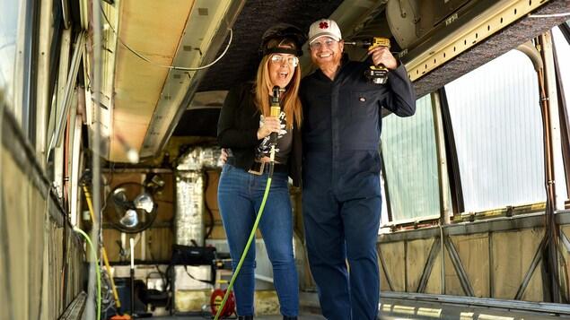 Une femme et un homme tenant des outils dans leurs mains dans un autobus en rénovation.