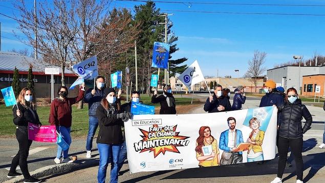 Une dizaine d'enseignants posent derrière une banderole sur laquelle il est écrit : « Faut que ça change maintenant! »