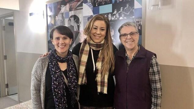 Trois femmes sont debout et sourient en regardant la caméra.