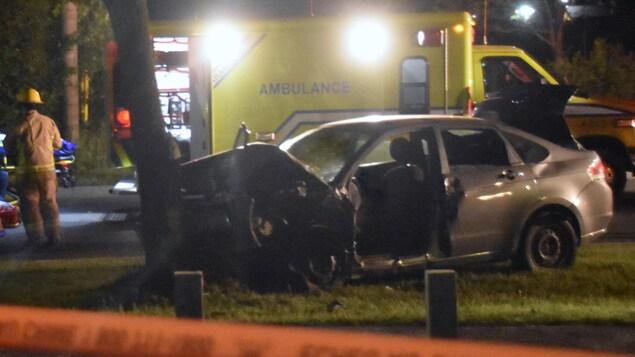 Une voiture qui a percuté un arbre, un pompier à gauche et une ambulance derrière.