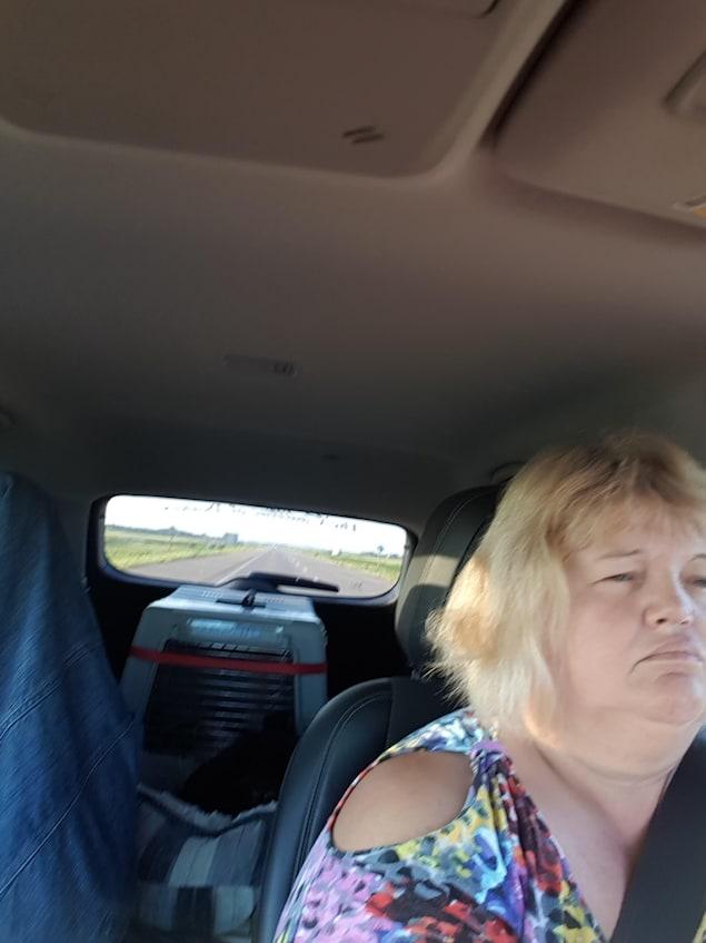 Brigitte dans sa voiture avec une cage en arrière
