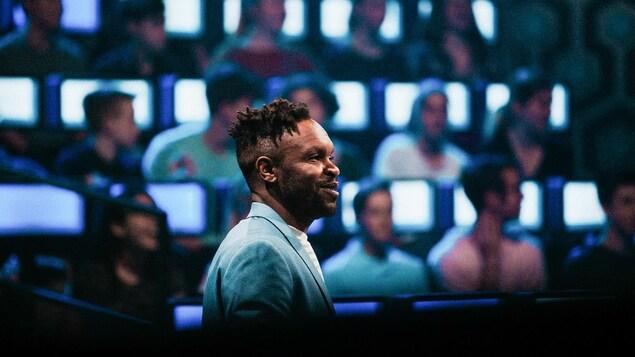 Portrait de l'animateur sur le plateau de l'émission avec les génies en arrière-plan.