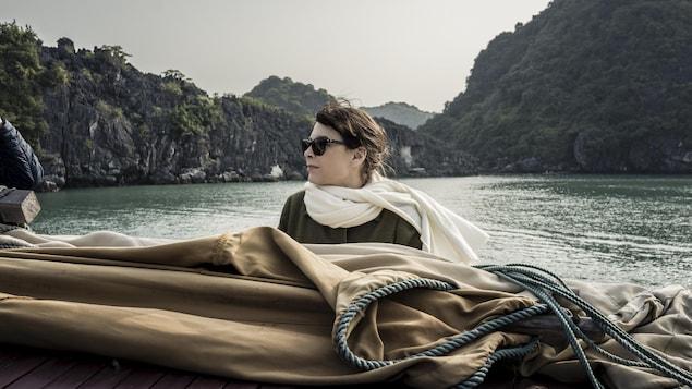 Une femme (Anne Dorval) avec des lunettes de soleil, sur le pont d'une barque sur l'eau.