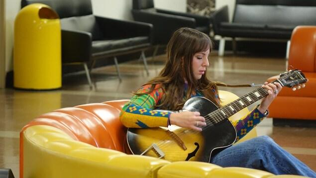 Une jeune femme joue de la guitare, assise sur un sofa jaune et orange dans une salle d'attente d'aéroport.