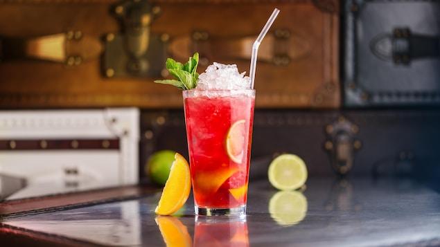 Un verre contenant un cocktail avec de la glace, une paille et des agrumes.