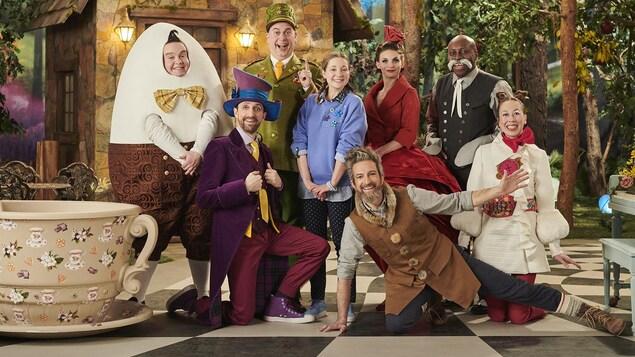 Les personnages posent tout sourire devant le décor d'une forêt et d'une maisonnette.