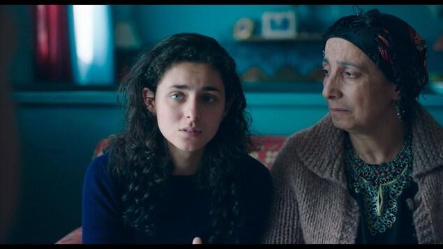 Une jeune fille (Nahéma Ricci) assise à côté d'une plus vieille femme qui la regarde.