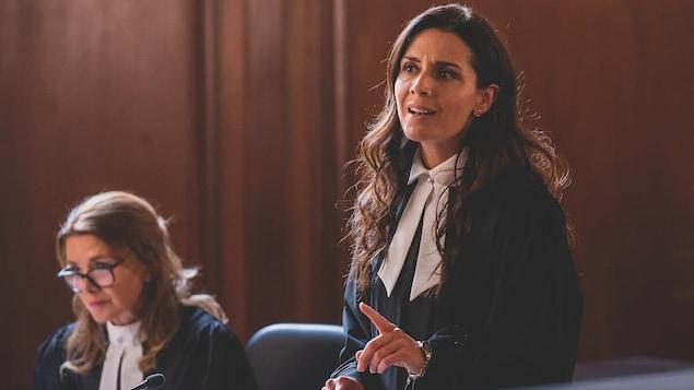 Une avocate debout, en cour, en train de plaider. Une autre avocate est à côté d'elle, assise.