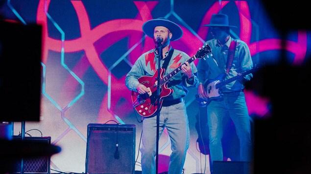 Un guitariste porte un grand chapeau tout comme le bassiste derrière lui.
