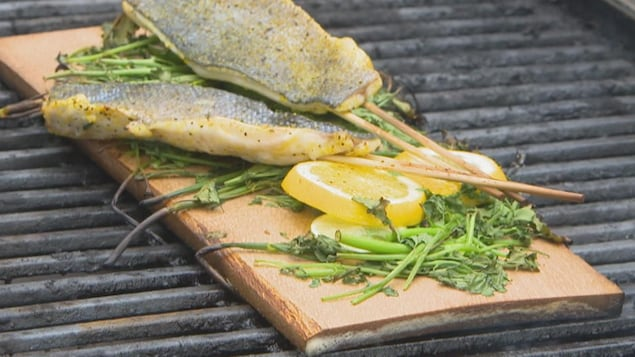 Des brochettes de poisson sur un barbecue.