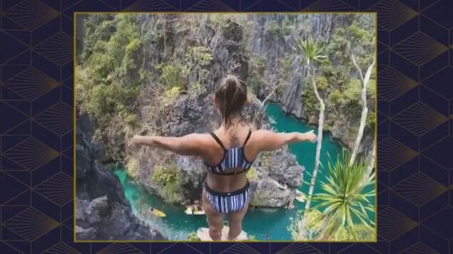 Du haut d'une falaise, la plongeuse Lysanne Richard lève les bras en se préparant à sauter.