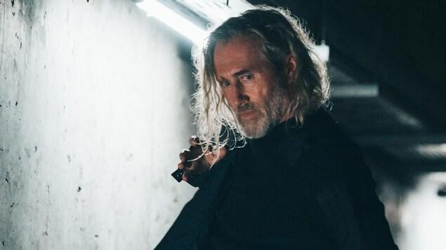 Un homme (Roy Dupuis) en tenue noire dans un couloir de béton.