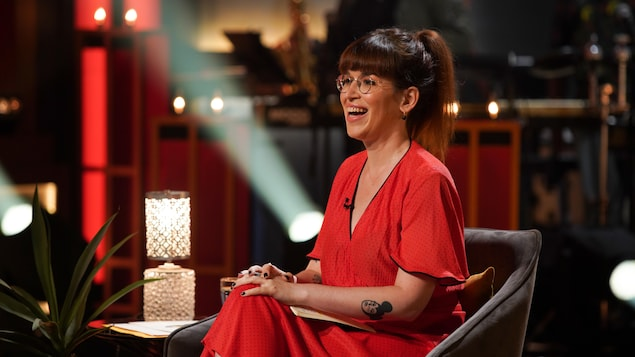 La femme habillée d'une robe rouge est assise dans un fauteuil dans un studio de télévision et elle rit.