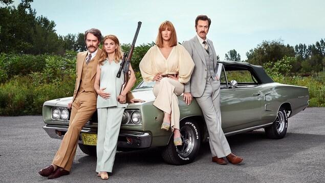 Les quatre personnages sont à côté d'un vieux modèle de voiture.