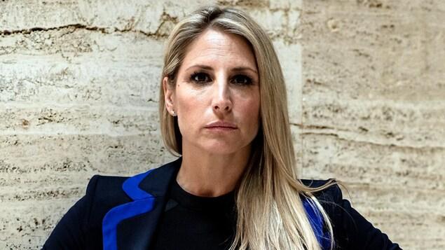 Gros plan sur une femme à l'air sérieux aux longs cheveux blonds. Elle porte une robe noire et une veste noire à bordure bleue.