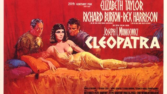 Sur fond rouge, la reine d'Égypte est allongée devant César et Marc-Antoine