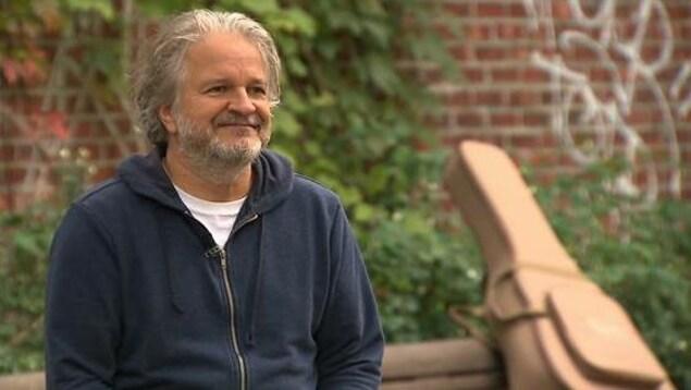 Il est dehors devant un mur de briques orné de plantes grimpantes et de graffitis. L'étui de sa guitare est sur le banc a côté de lui.