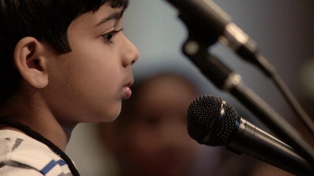 Un jeune garçon devant un micro.