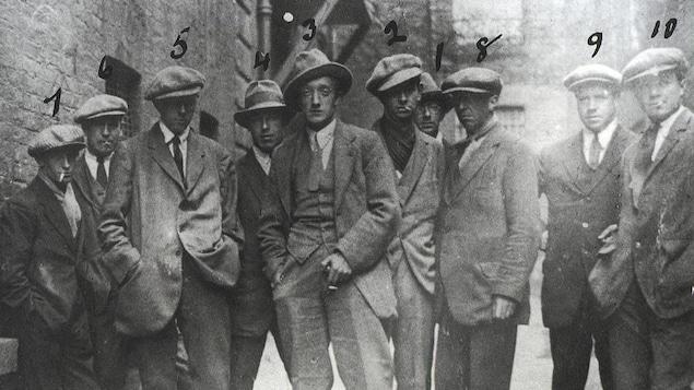 Dans une ruelle, 10 hommes en habits d'époque de 1920.