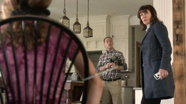 Jean Raymond qui pointe son fusil sur Gabrielle. Gabrielle découvre sa fille Emma Simard bâillonnée sur une chaise.