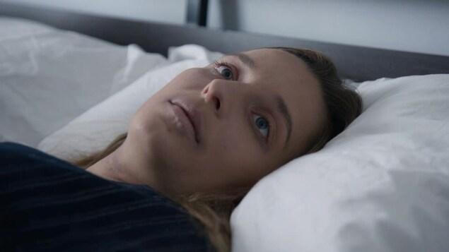 Virginie Francoeur, couchée dans le lit, les yeux ouverts.