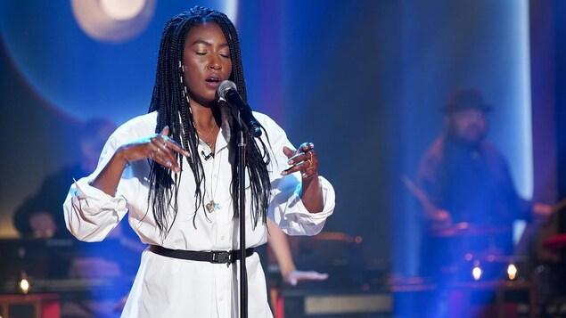Une femme qui chante les yeux fermés.