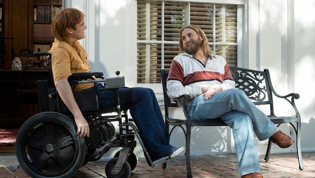 Un homme assis dans une chaise roulante et un autre assis sur un banc.