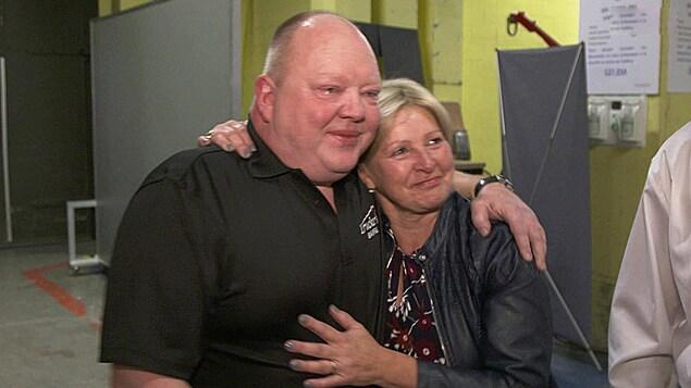 Un homme avec les larmes aux yeux prend sa femme par l'épaule.