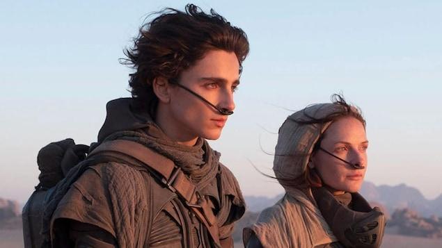 Un jeune homme (Timothée Chalamet) et une femme (Rebecca Ferguson) avec des systèmes de respiration dans le nez regardent vers l'horizon à droite.